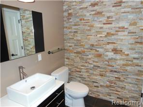 Lower level full bath featuring high-end fixtures & stone wall.