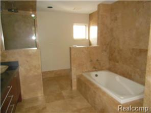 Bath features soaker tub, separate stone & glass shower.