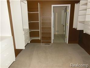 Huge master closet with built-ins leads to laundry room.
